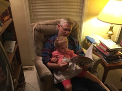 My dad in his element, reading to his granddaughter.
